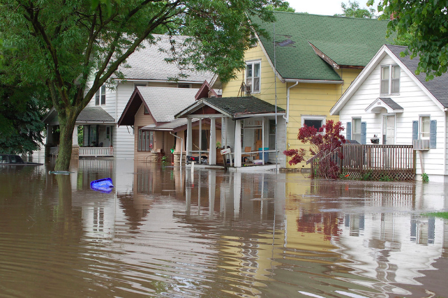 This image showcases a flooded neighborhood in Cedar Rapids, Iowa, captured by the U.S. Geological Survey. Four houses are shown in the photograph. Flood waters rise above the porch level of each home. In some cases, stairwells are completely covered by stormwater.