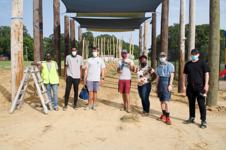 Seven adults wearing masks pose at construction site