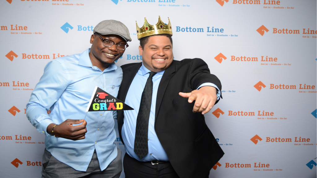In front of a step and repeat that features the organe Bottom Line logo stand two men, arm in arm, one darker skinned and wearing a light blue button down shirt and a grey beret who holds a small pendent flag that reads congrats grad. The other man is lighter skinned, wearing a black suit, and a toy crown on his head.