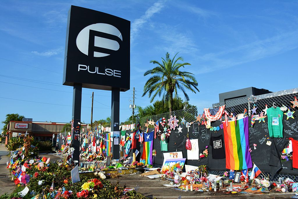 A scene of the Pulse nightclub in Orlando, Florida in 2016 after the deadliest attack on the LGBTQ+ community on our nation's history. A large number of memorials to the victims of the shooting are left on the fence and ground outside the club, including flowers, signs, photos, cards, Pride and American flags.