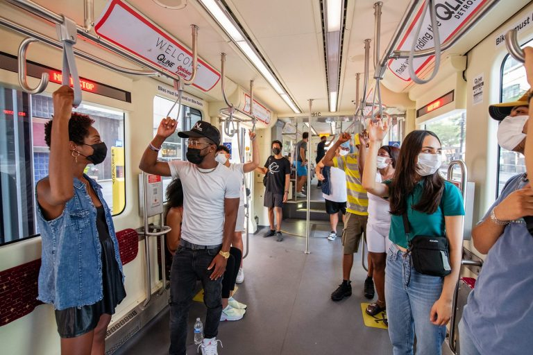 A diverse group of riders inside one of Detroit's QLine streetcars. All of them are masked and standing, holding on to straps and rails.