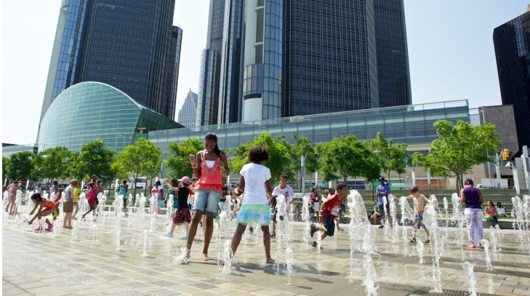 Children are playing among a series of water spouts in the General Motors Plaza along the Detroit Riverwalk in front of the Renaissance Center.