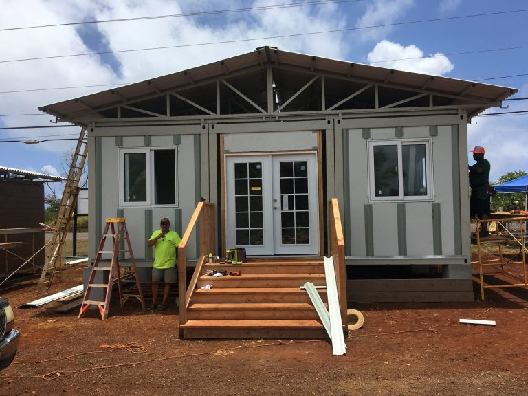 A photo of two people working on a house being built in Hawaii.