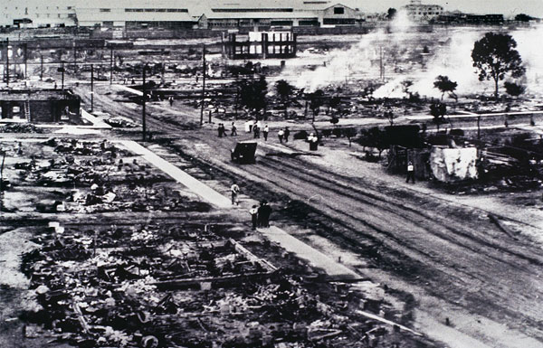 The aftermath of the Tulsa Race Massacre in 1921 where white mobs murdered hundreds of Black citizens and burned down a thriving Black neighborhood in Tulsa, Oklahoma. The black and white photo depicts a street in the Greenwood area with the charred remains of multiple homes and businesses and smoke rising from the ashes in the background.