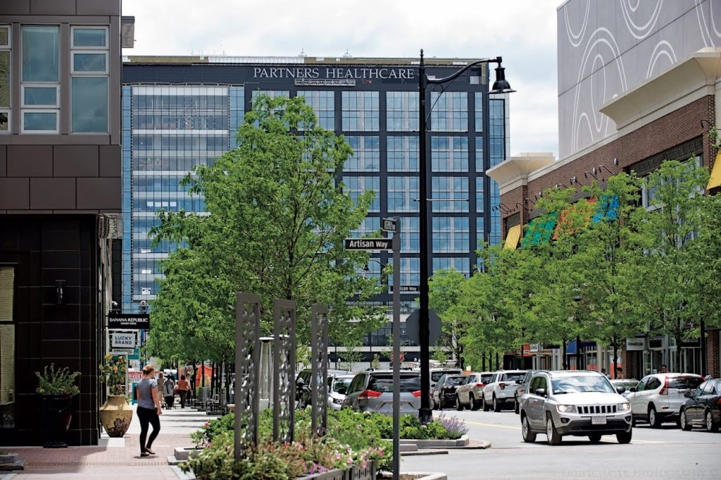 """The image shows a city street, with green trees on each side. At the end of the street is a black office building with the words """"Partners Healthcare"""" at the top."""