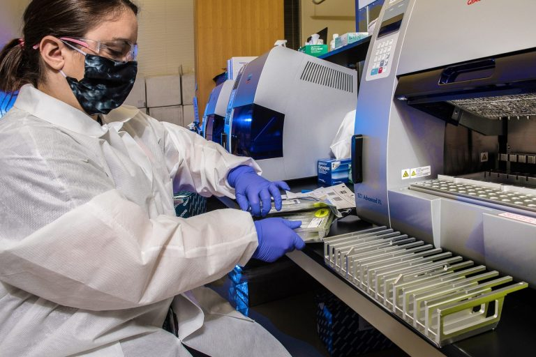 A woman at the left of the photo wearing goggles, a mask, a white lab coat and purple safety gloves sits in front of a silver machine with several pipettes lined up in front of her on a counter.