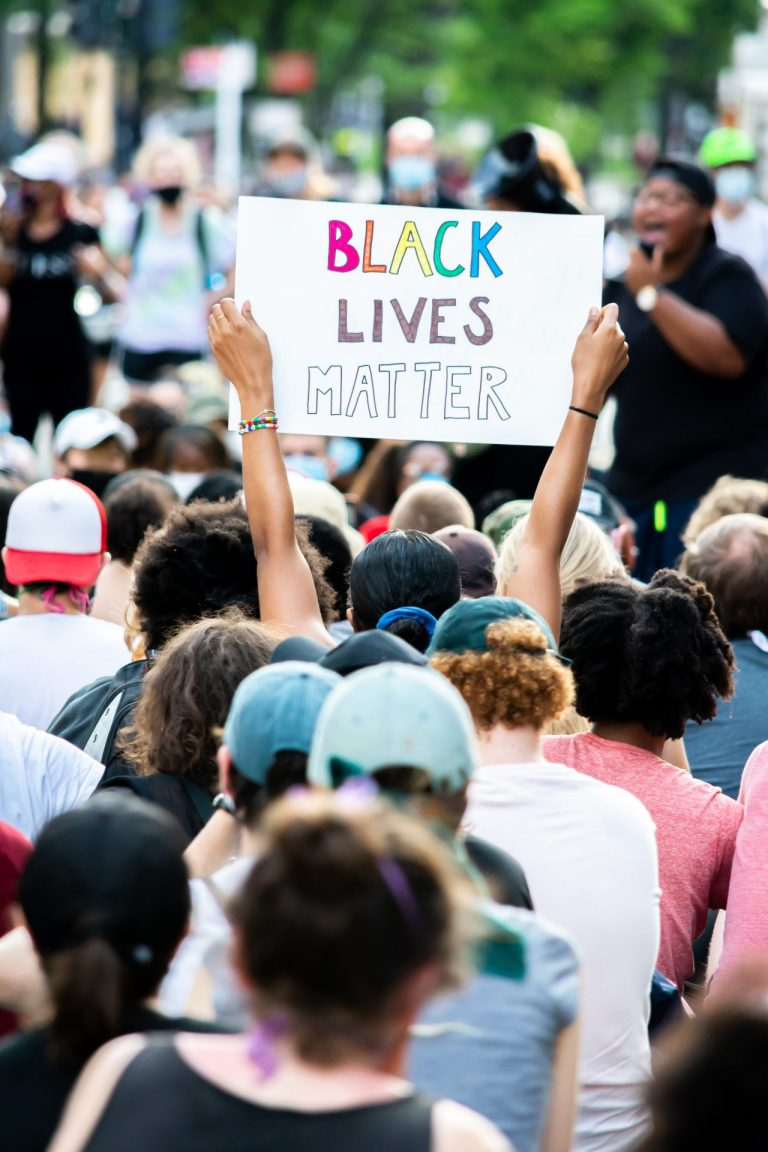 A large crowd of protesters on Pennsylvania Avenue in Washington, D.C. that are seen from behind, at a Black Lives Matter protest. A person holds up a sign above the crowd with the words Black Lives Matter in colorful letters.