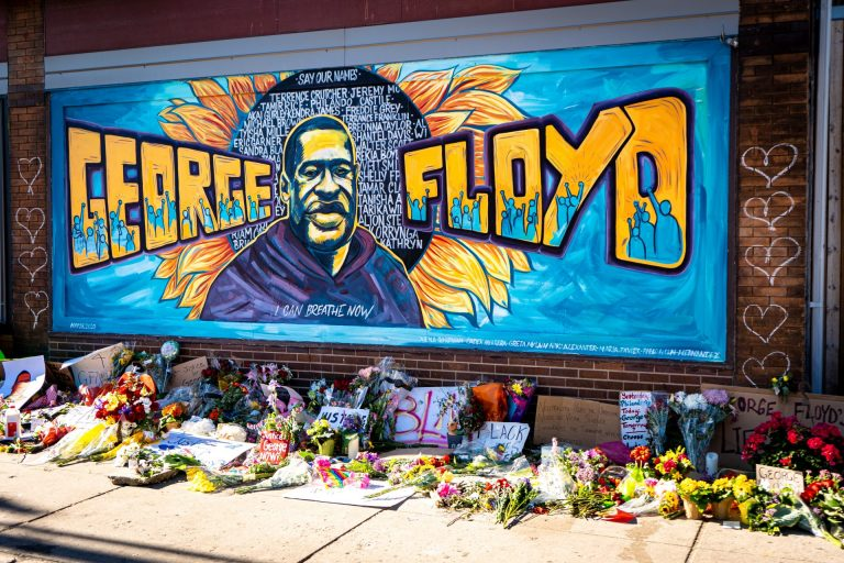 A colorful mural on a brick wall honoring the life of George Floyd. It has the words George Floyd and his image in the middle with a flower behind that has a dark center with the words 'Say our names' and a list of names of people who lost their lives at the hands of the police. There are images of people raising their fists in the letters of George Floyd's name. There are images of hearts in chalk on the wall and tributes of flowers, balloons and signs below the mural on the sidewalk.