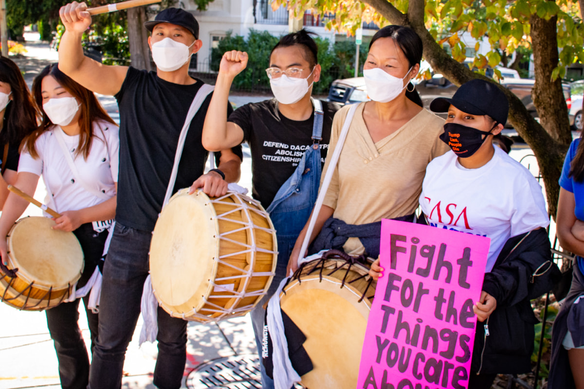 seven individuals standing on a sidewalk, wearing masks under a tree, with three people holding drums and one holding a sign that reads fight for the things you care about